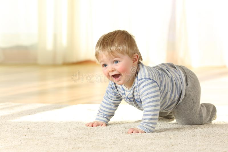 Happy baby crawling and laughing on a carpet royalty free stock photography