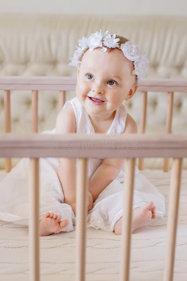 A happy baby in a dress sits in a crib. And laughs royalty free stock photos