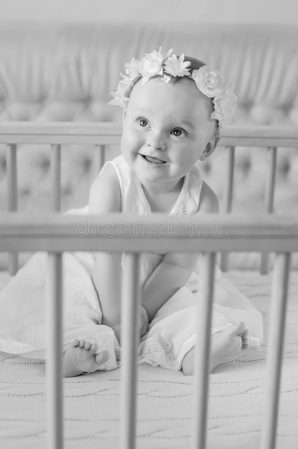 A happy baby in a dress sits in a crib. And laughs black and white stock image