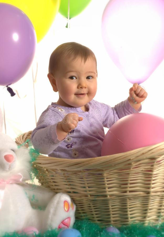 Happy baby in an Easter basket royalty free stock image