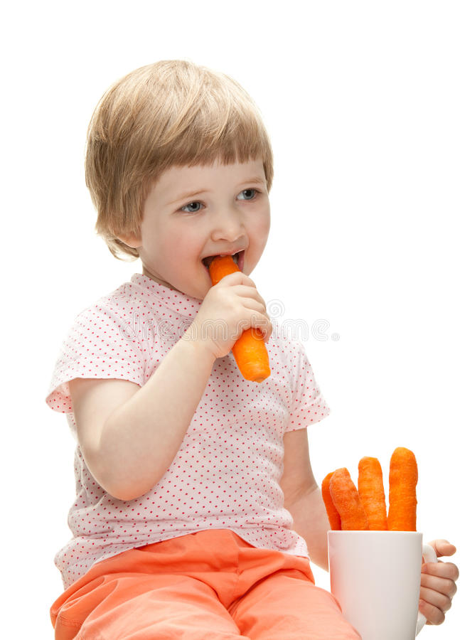Happy baby eating fresh carrot royalty free stock photos