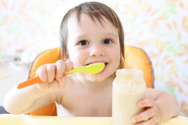 Happy baby eating fruity puree royalty free stock image