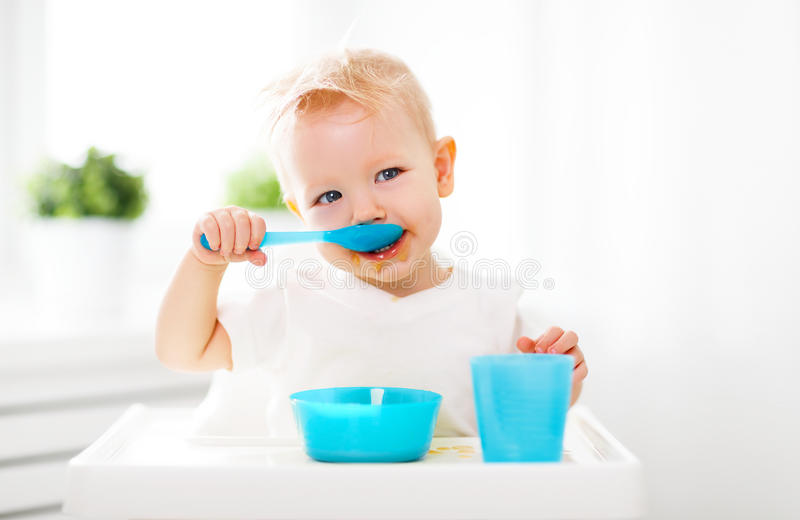 Happy baby eating himself stock photography