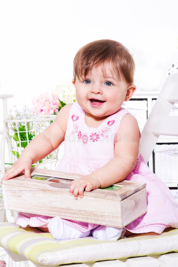 Happy baby in festive dress. Happy baby in a festive dress holding wooden box royalty free stock image