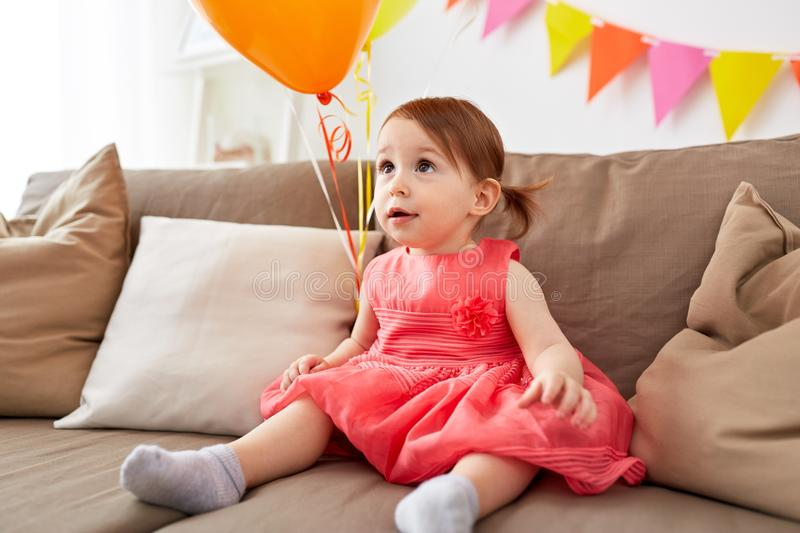 Happy baby girl on birthday party at home. Childhood, holidays and people concept - happy baby girl on birthday party at home royalty free stock photo