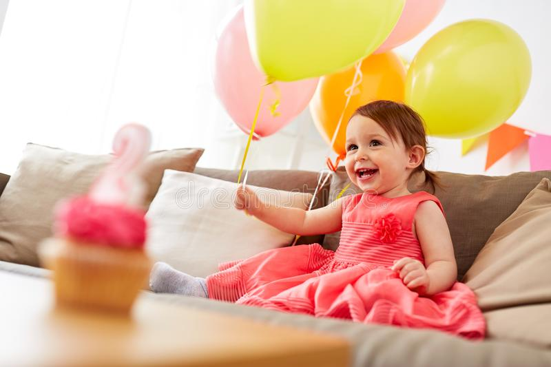 Happy baby girl on birthday party at home. Childhood, holidays and people concept - happy baby girl with air balloons, garland and cupcake on birthday party at stock photos