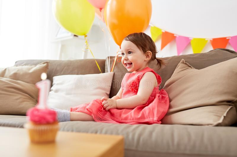 Happy baby girl on birthday party at home. Childhood, holidays and people concept - happy baby girl air balloons and garland on birthday party at home royalty free stock image