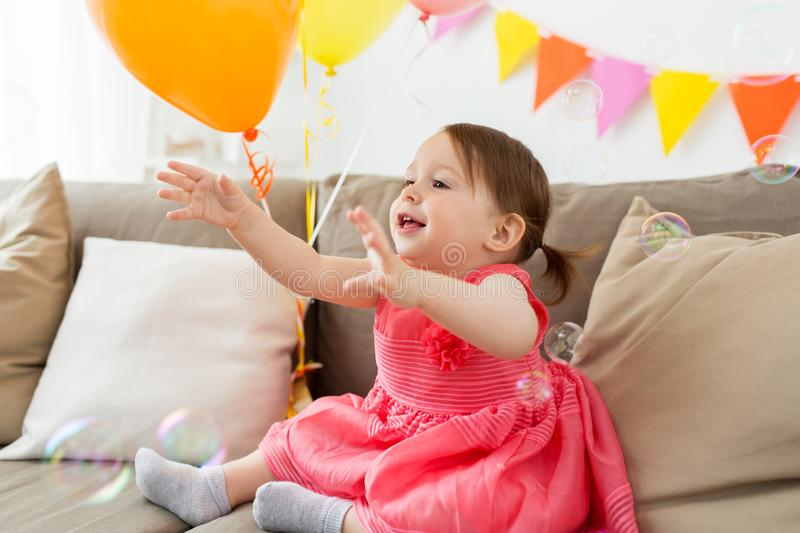 Happy baby girl on birthday party at home. Childhood, people and celebration concept - happy baby girl on birthday party at home royalty free stock photo