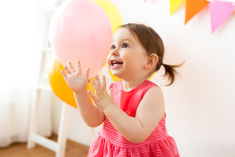 Happy baby girl on birthday party at home. Childhood, people and celebration concept - happy baby girl on birthday party at home stock photos