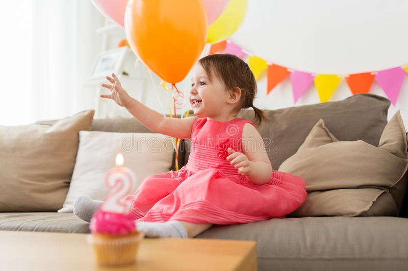 Happy baby girl on birthday party at home. Childhood, people and celebration concept - happy baby girl on birthday party at home stock photo