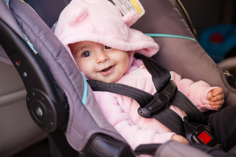 Happy baby girl in a car seat. Portrait of a beautiful baby girl sitting on a car seat and smiling stock image