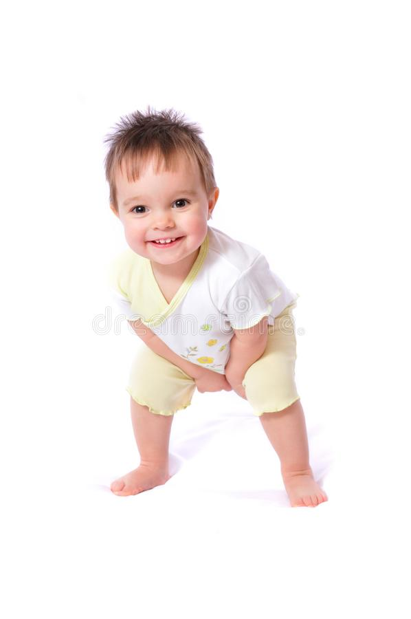 Happy baby girl in child wear bending down. Standing happy little one year baby girl in white t-shirt and yellow shorts bending down. Isolated on white stock images