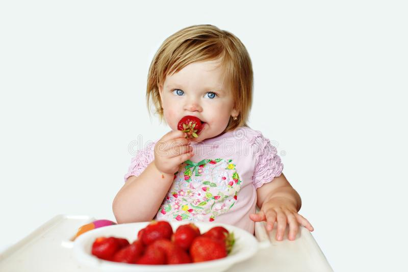 Baby  girl   eating strawberry stock images