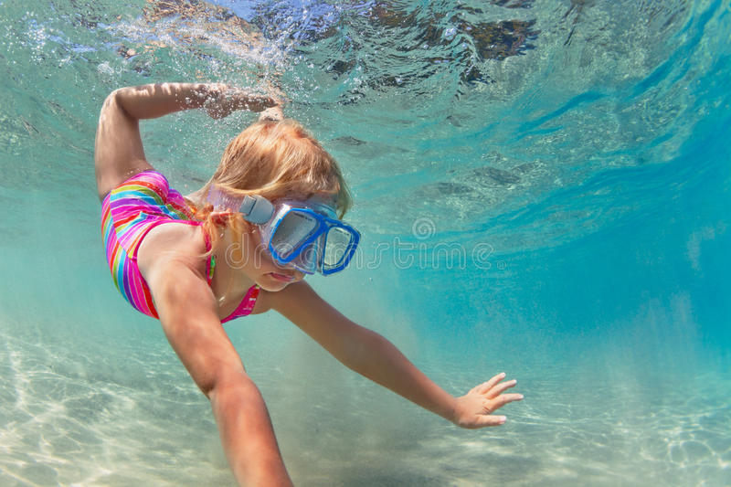 Happy baby girl dive underwater in sea pool. Happy baby girl in snorkeling mask dive underwater with fun in sea pool. Healthy lifestyle, people water sport royalty free stock photography