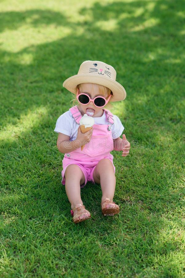 Happy baby girl dressed pink summer clothes, yellow hat and pink sunglasses sits on a green lawn and eats white ice royalty free stock photos