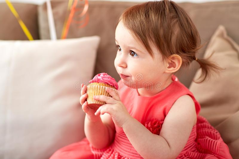 Happy baby girl eating cupcake on birthday party. Childhood, holidays and people concept - happy baby girl eating cupcake on birthday party at home royalty free stock images