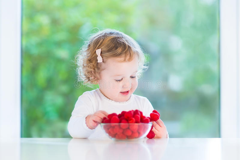 Happy baby girl eating raspberry at white table royalty free stock images