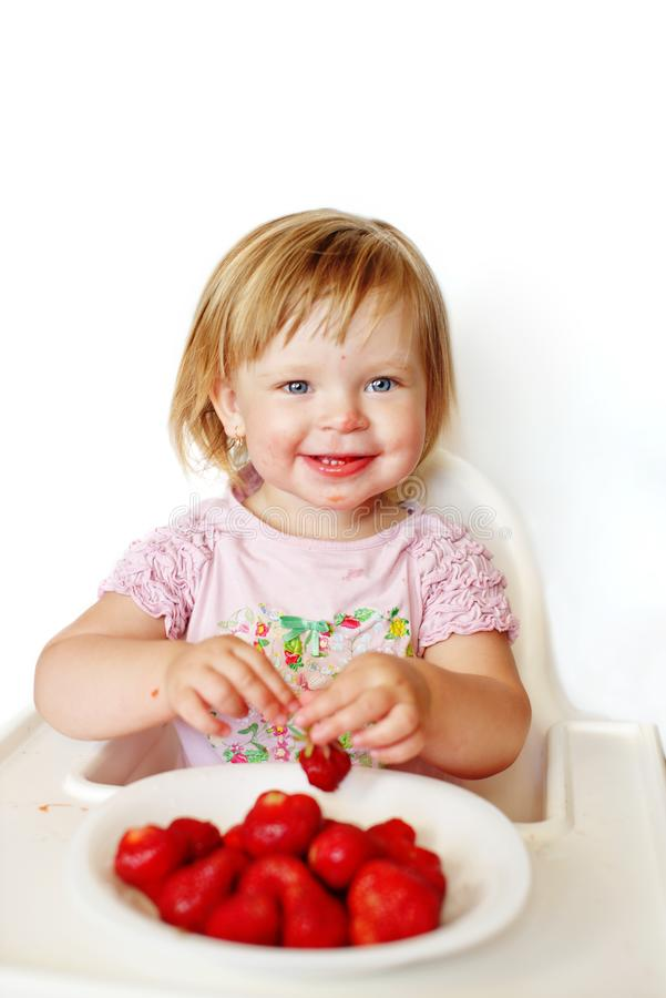 Baby  girl eating strawberry royalty free stock photo