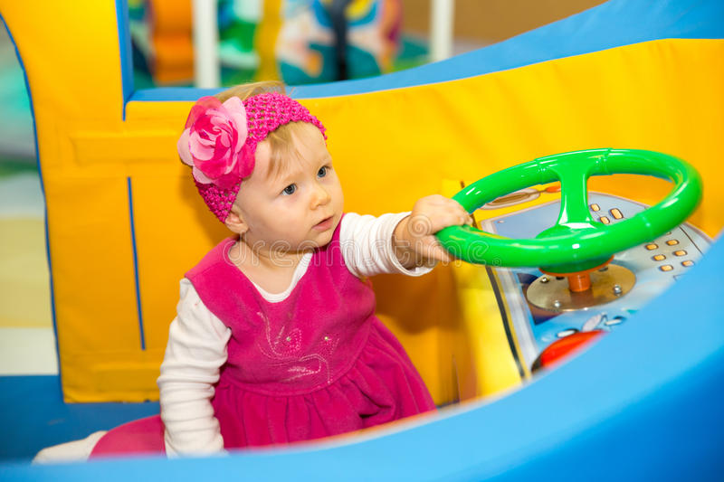 Happy baby girl keep on board ship on playground stock photo