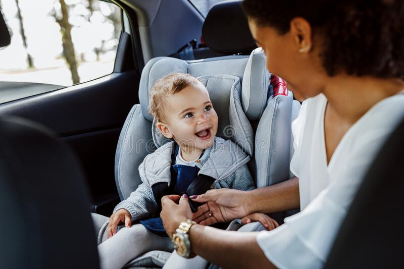 Happy baby girl looking at her mother in a car royalty free stock image