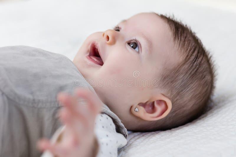 Happy baby girl lying on back stock images