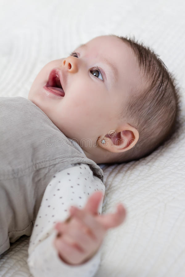Happy baby girl lying on back over white bedcover. Happy cute baby girl lying on back over white bedcover stock photos