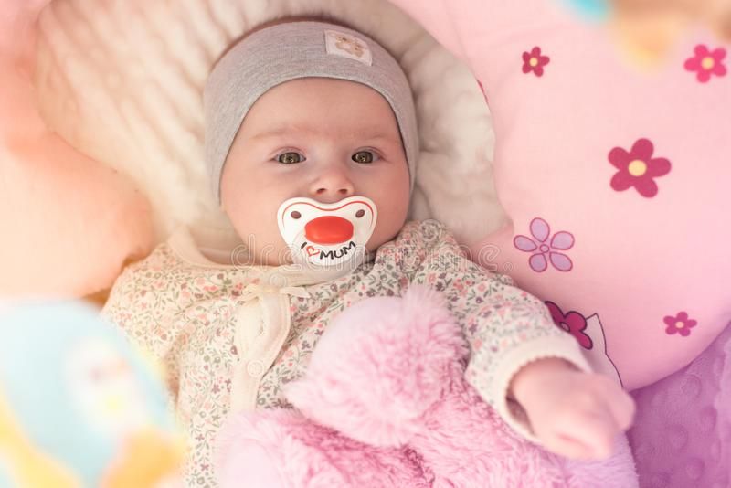 Happy baby girl lying in his crib with soother and pink bear stock photos