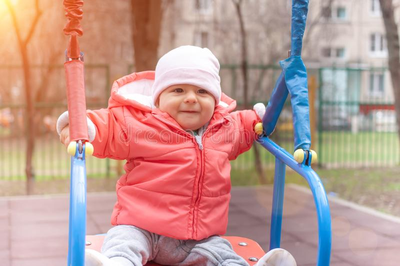 Happy baby girl in pink jacket swinging in swings. Sunny spring day royalty free stock images