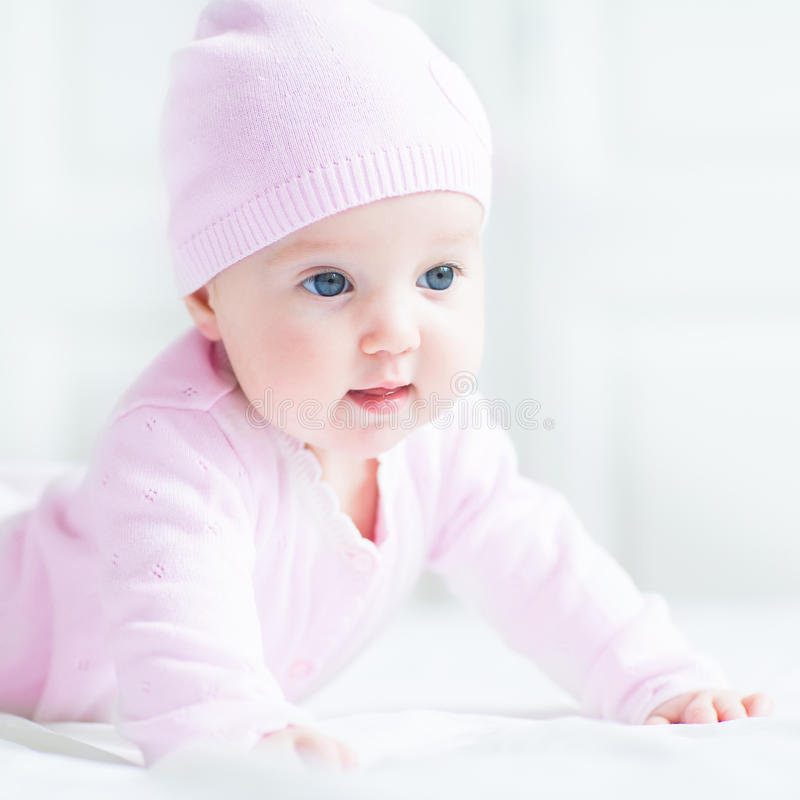 Happy baby girl in a pink knitted hat royalty free stock photo