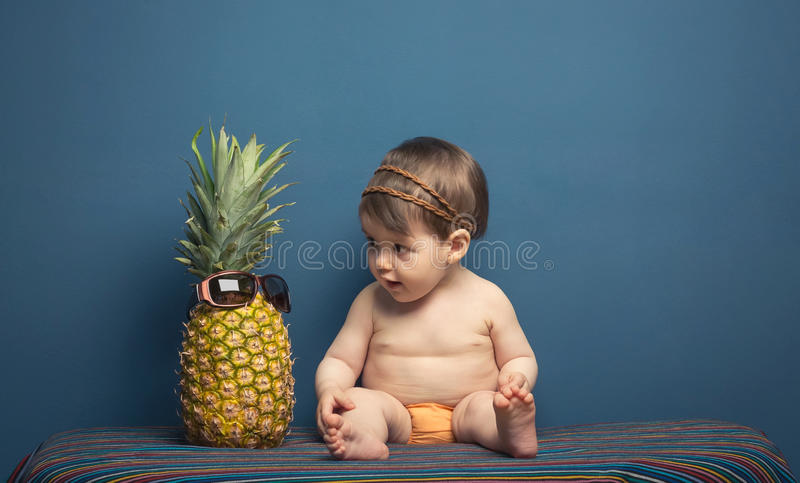Happy baby girl playing with a pineapple stock photography