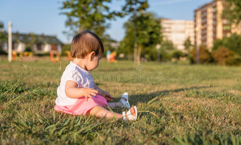 Happy baby girl playing sitting on a grass park. Adorable baby girl playing sitting on the grass park in a sunny summer day royalty free stock image