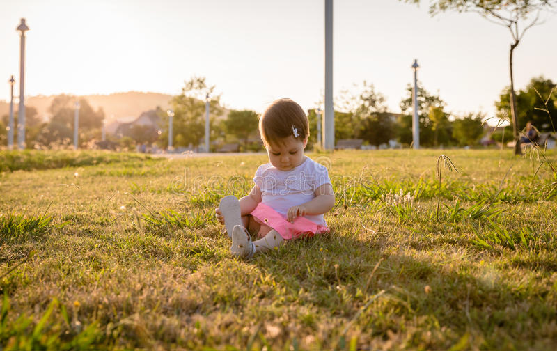 Happy baby girl playing sitting on a grass park. Adorable baby girl playing sitting on the grass park in a sunny summer day royalty free stock photos