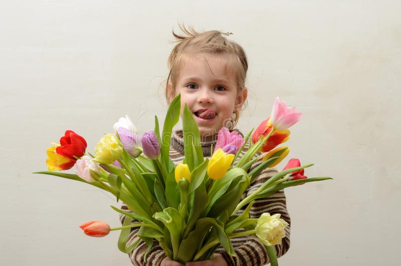 Happy baby girl rejoices and smiles with a bouquet of multi-colored tulips in hands royalty free stock photography