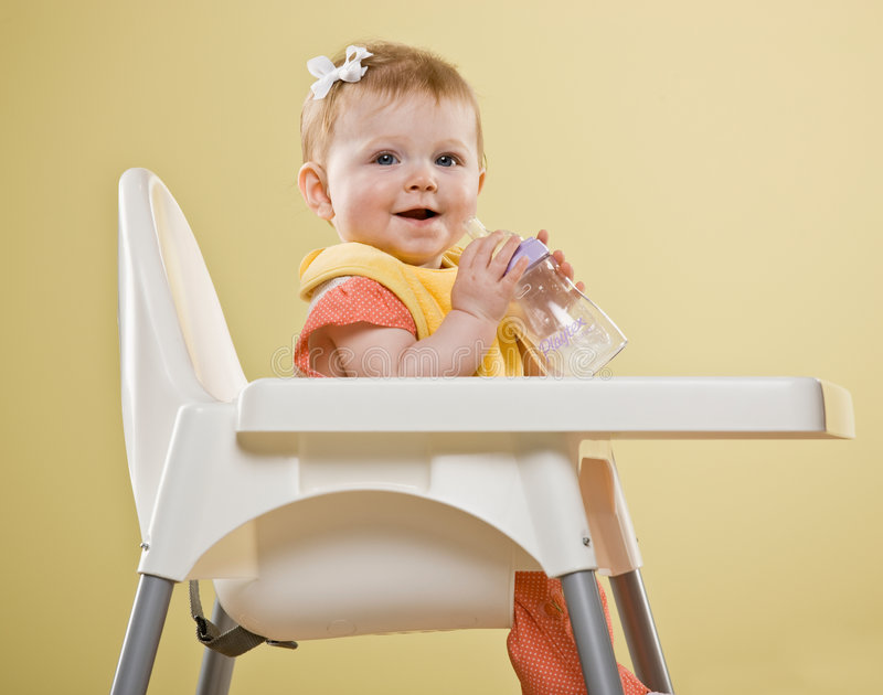 Happy baby girl sitting in highchair. Holding bottle royalty free stock photo