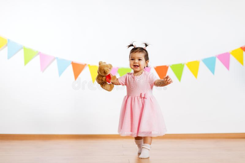 Happy baby girl with teddy bear on birthday party. Childhood, people and celebration concept - happy baby girl with teddy bear toy on birthday party stock images
