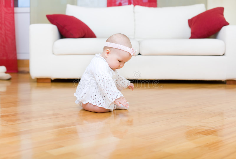 Happy baby girl touch a floor. Happy baby girl touch a hardwood floor royalty free stock photography
