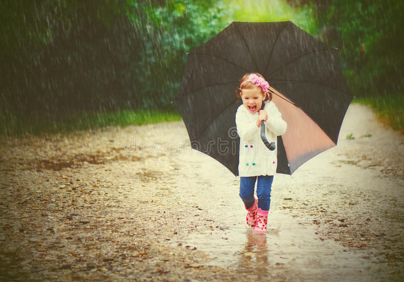 Happy baby girl with an umbrella in the rain runs through. The puddles royalty free stock photo