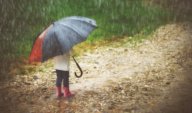 Happy baby girl with umbrella in the rain runs through. Happy baby girl with an umbrella in the rain runs through the puddles royalty free stock photo
