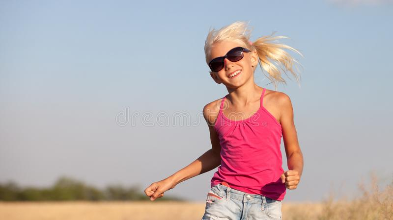 Happy baby girl with white hair running along the wheat field in stock photo