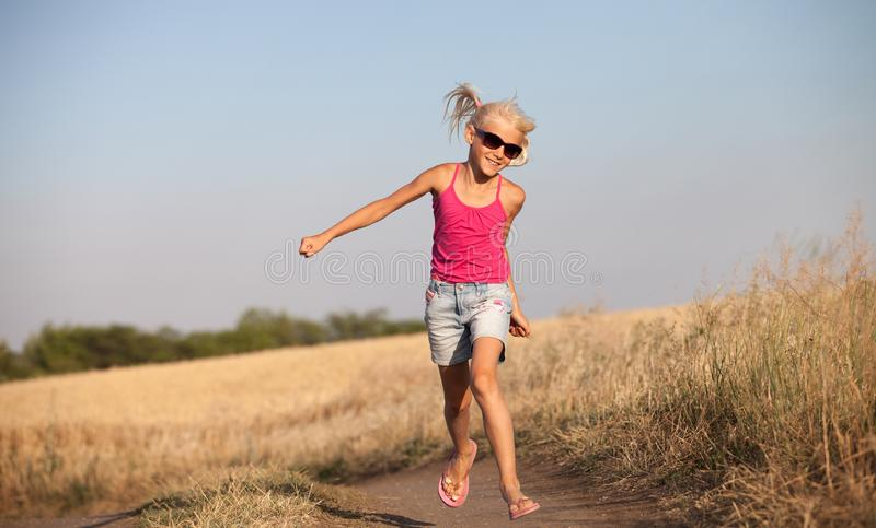 Happy baby girl with white hair running along the wheat field in stock image