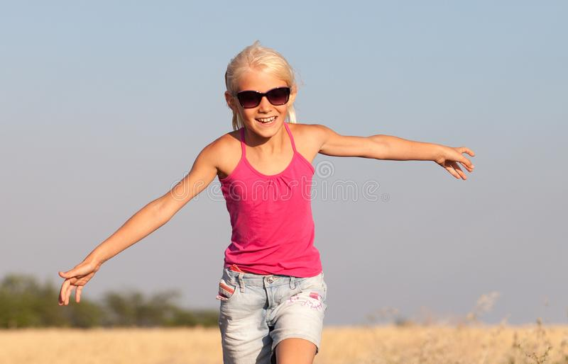 Happy baby girl with white hair running along the wheat field in stock photos