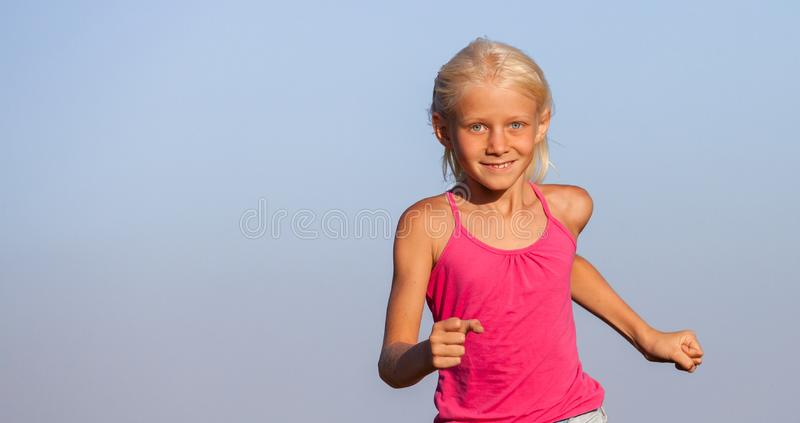 Happy baby girl with white hair running along the wheat field in royalty free stock photo