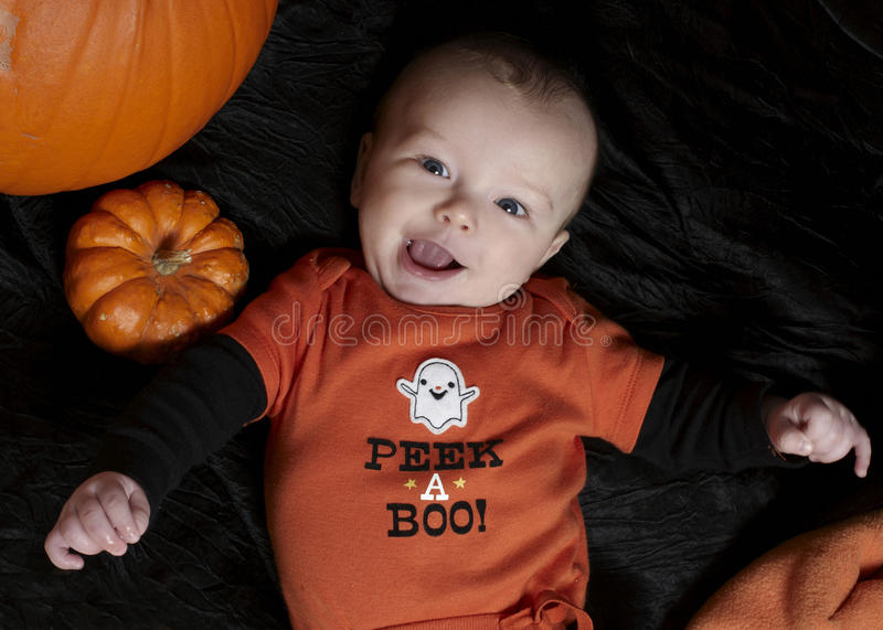 Happy baby on halloween. Happy baby for his first Halloween. Baby's first Halloween. Excited baby. Boo! pumpkins around baby stock photography
