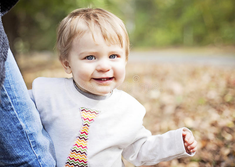 Happy baby holding on to parent royalty free stock photo
