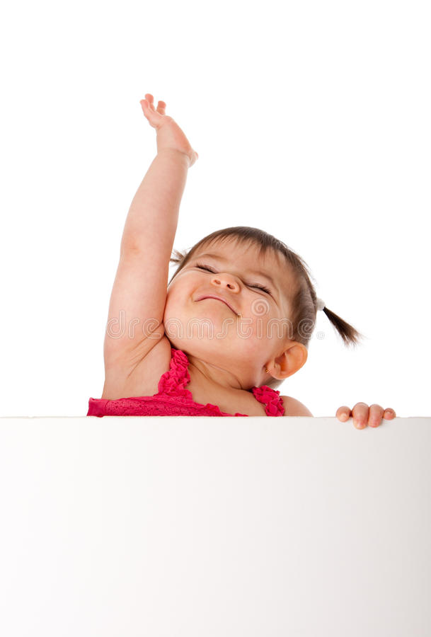 Happy baby holding white board and reaching up. Cute beautiful happy baby infant girl holding white board while reaching up in the air with pride, isolated royalty free stock image