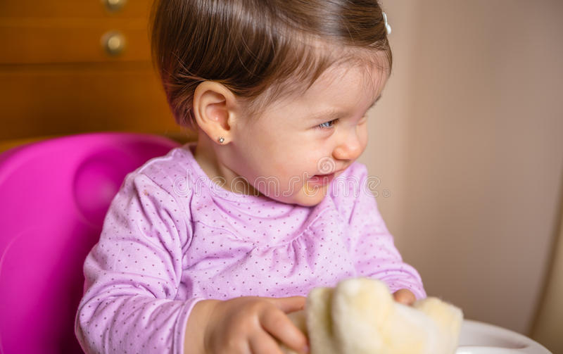 Happy baby laughing and playing with a toy sitting royalty free stock image