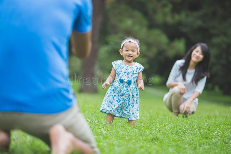 Happy baby making his first steps on a green grass stock photo