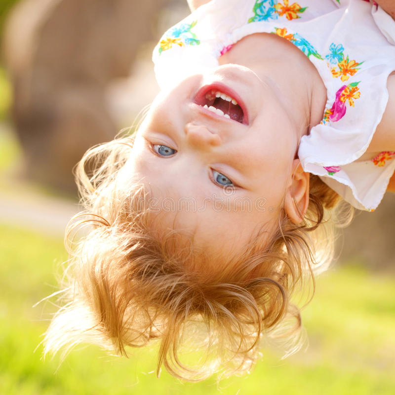 Happy baby playing upside down. Happy baby playing and laughing upside down stock image