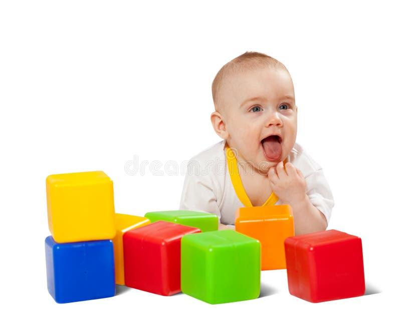 Happy baby plays with toy blocks stock photos