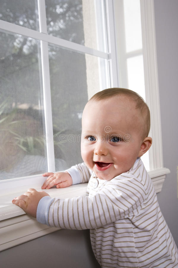 Happy baby pulling himself up on window sill stock photos